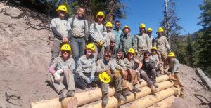 Southwest Corps members group shot among logs