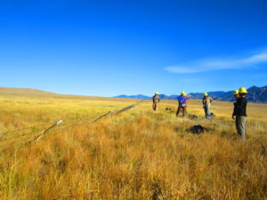 Eleven Mile Project - photo of the prairie and mountains in the back, crew working in the field