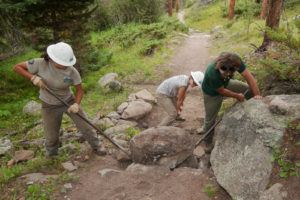North Inlet Trail project - people working on clearing stone and logs along a trail